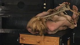 Blonde military babe hangs from bindings and gets spanked by hooded soldier.